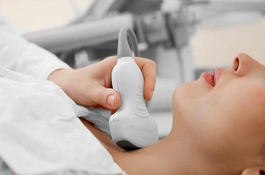 Ultrazvuk vratnog dela kao ilustracija za ultrazvuk i ultrazvučni pregled. Ultrazvučna sonda kojom upravlja lekar specijalista je u predelu vrata ženskog pacijenta