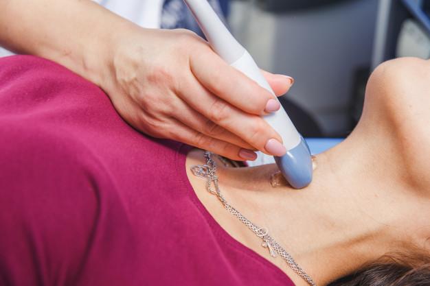 Ultrazvučni pregled endokrinologa sa ultrazvučnom sondom u predelu vrata